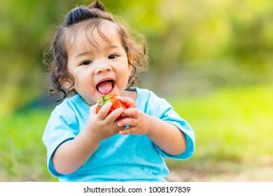 little girl happy eating tomato over green background