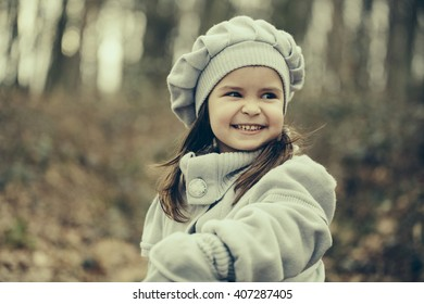 Little girl with happy face in coat and hat walking in autumn forest