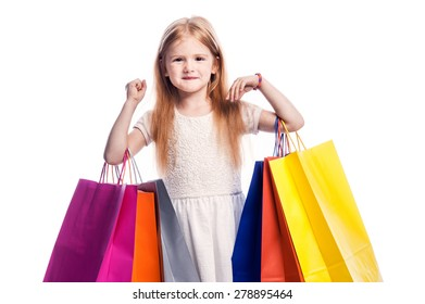 Little girl happy with her shopping. Studio shot on white background.