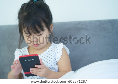 Little girl happy look smart phone. asian child.Child development.