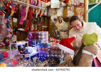 Little girl with happy mom in Christmas market. Focus on woman