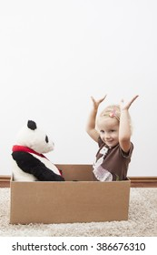 little girl is happy to move, with panda bear on cardbox