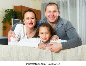 Little girl with happy parents posing in livingroom at home and smiling. Focus on girl