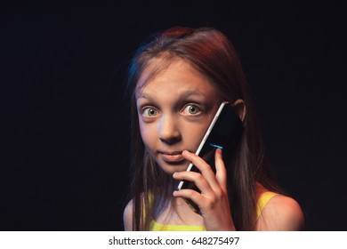Little girl with a happy and surprised face talking on the phone