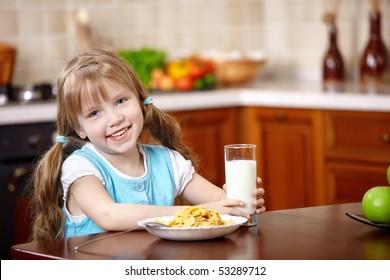 The little girl has breakfast on kitchen