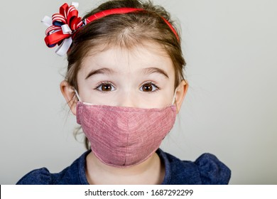 Little girl has fabric mask protect herself from Coronavirus COVID-19, child with a mask on her nose for safety outdoor activity, illness or air pollution