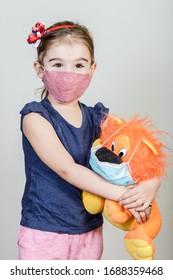 Little girl has fabric mask protect herself from Coronavirus COVID-19, child with a mask for safety.Studio shot with her toy in mask.