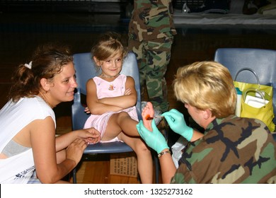 Little girl has foot treated at a Biloxi shelter after Hurricane Katrina. Taken in Biloxi, MS on September 6, 2005.