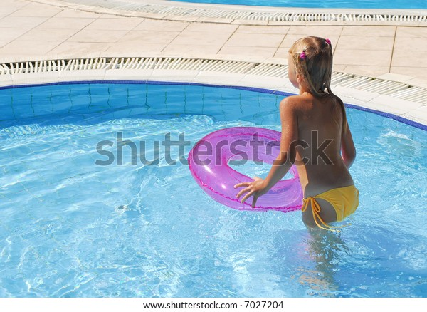 The little girl has a rest near pool