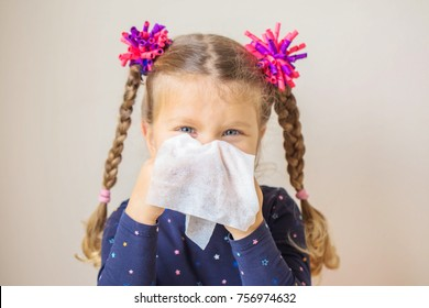 The little girl has a runny nose and blows her nose into a paper handkerchief. Children's cold, selective focus on a handkerchief. Acute respiratory viral infection.