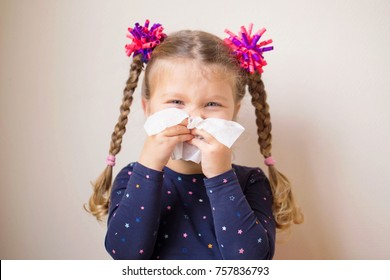 The little girl has a runny nose and blows her nose into a paper handkerchief. Children's cold, selective focus on a handkerchief. Acute respiratory viral