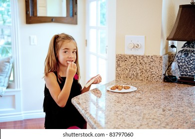 Little girl has a snack of cookies and string cheese in the kitchen after school