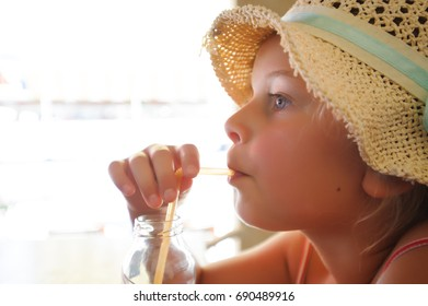 little girl with hat drinking with straw
