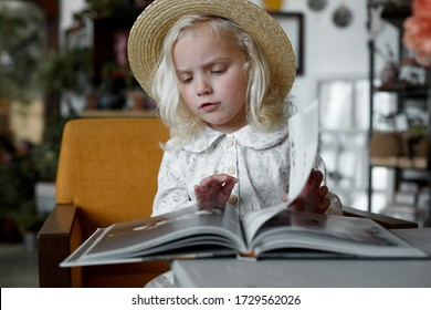 a little girl in a hat leafing through a book