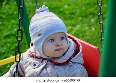Little girl in hat on swing