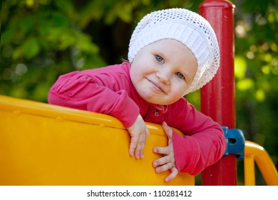 Little girl in hat playing on the playground