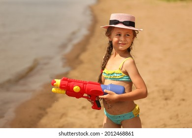 A little girl in a hat is standing on the beach with a water pistol in her hands