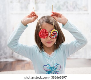Little girl have fun with lollipops