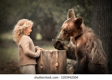 Little girl have met a real bear in the forest and talk with him. Image with selective focus and toning