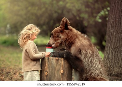 Little girl have met a real bear in the forest and fed him with raspberry. Image with selective focus and toning