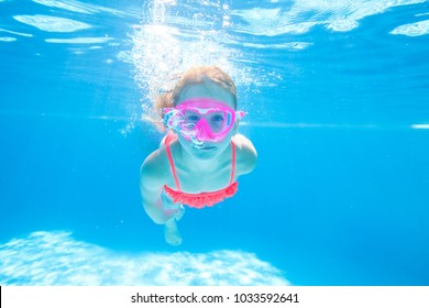 little girl having fun with bubbles in the pool.Underwater photo.