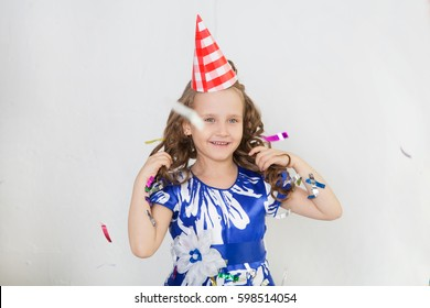 Little girl having fun celebrating birthday. Portrait of a child throws up multi-colored tinsel and confetti. Positive emotions.
