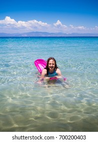 Little girl having fun durign summer holidays in the water of Aegean sea, Greek island of Thasos.