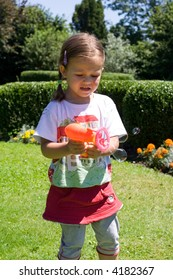 little girl having fun with making soap bubbles
