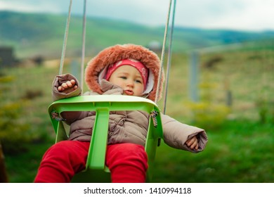 Little girl having fun on a swing on summer day
