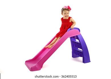 Little girl having fun on slide isolated on white