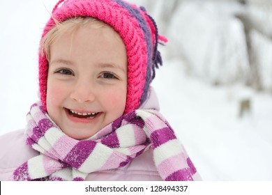 little girl having fun outdoors in the cold and snow