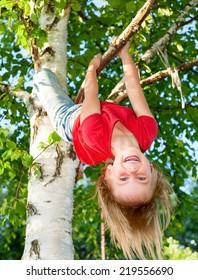 Little girl having fun playing on birch tree