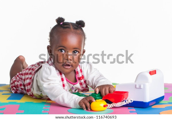A little girl having fun playing with a telephone on her letter carpet.