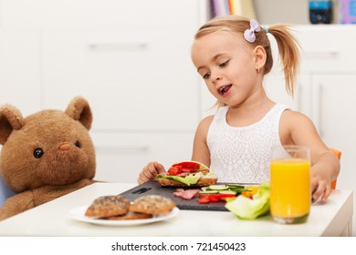 Little girl having a healthy snack sitting at the table with her toy bear assembling a fresh sandwich