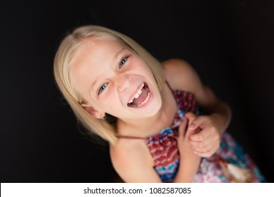 Little girl having a laugh wih her mouth wide open.