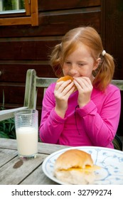 Little girl is having lunch with bread and milk