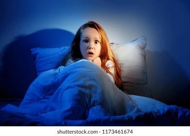 Little girl having nightmared sitting in her bed