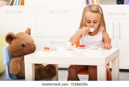 Little girl having some tea with her toy bear - sitting at a small table sipping from a cup, shallow depth