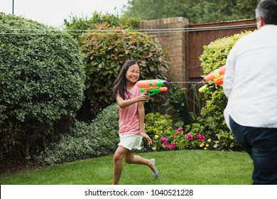 Little girl is having a water fight in the garden with her dad using water pistols.