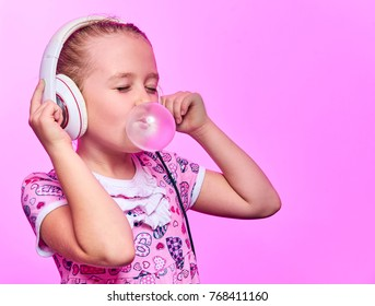 little girl with headphones blowing up a bubble of gum on a pink background