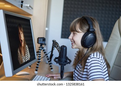 Little girl in headphones sitting at table working with computer using microphone, recording audio for video blog, interiors