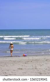 A little girl heads towards the shoreline on a beautiful Summer beach day.