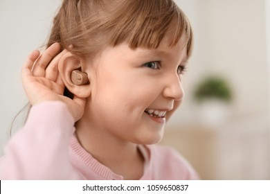 Little girl with hearing aid indoors
