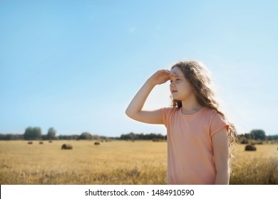 Little girl held out her hand and looks into the distance in a wheat field. Future, happy childhood, harvesting concept.
