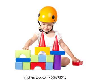 little girl in helmet building a house isolated on white