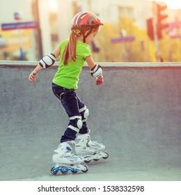Little girl in helmet on roller-skates in park