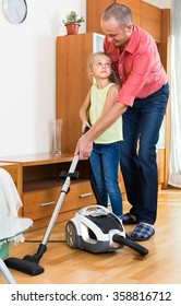 Little girl helping father to do regular clean-up indoors