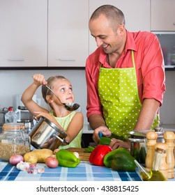 Little girl helping father to prepare salad  indoors