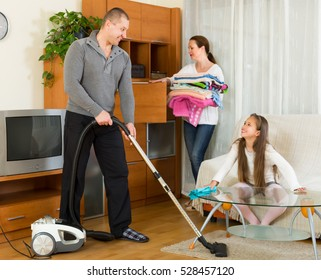 Little girl helping happy smiling parents to clean at home. Focus on man