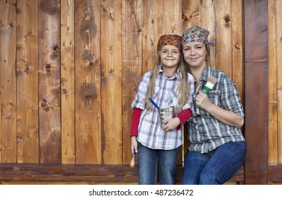 Little girl helping mother repainting the wood shed - happy family portrait